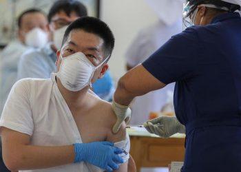 Una persona in Cina si fa inoculare il vaccino Sinopharm e Sinovac