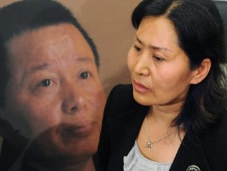 Geng He, moglie di Gao Zhisheng, davanti alla gigantografia del marito, scomparso in Cina