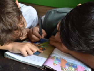 scuola, due studenti colorano un quaderno seduti al banco