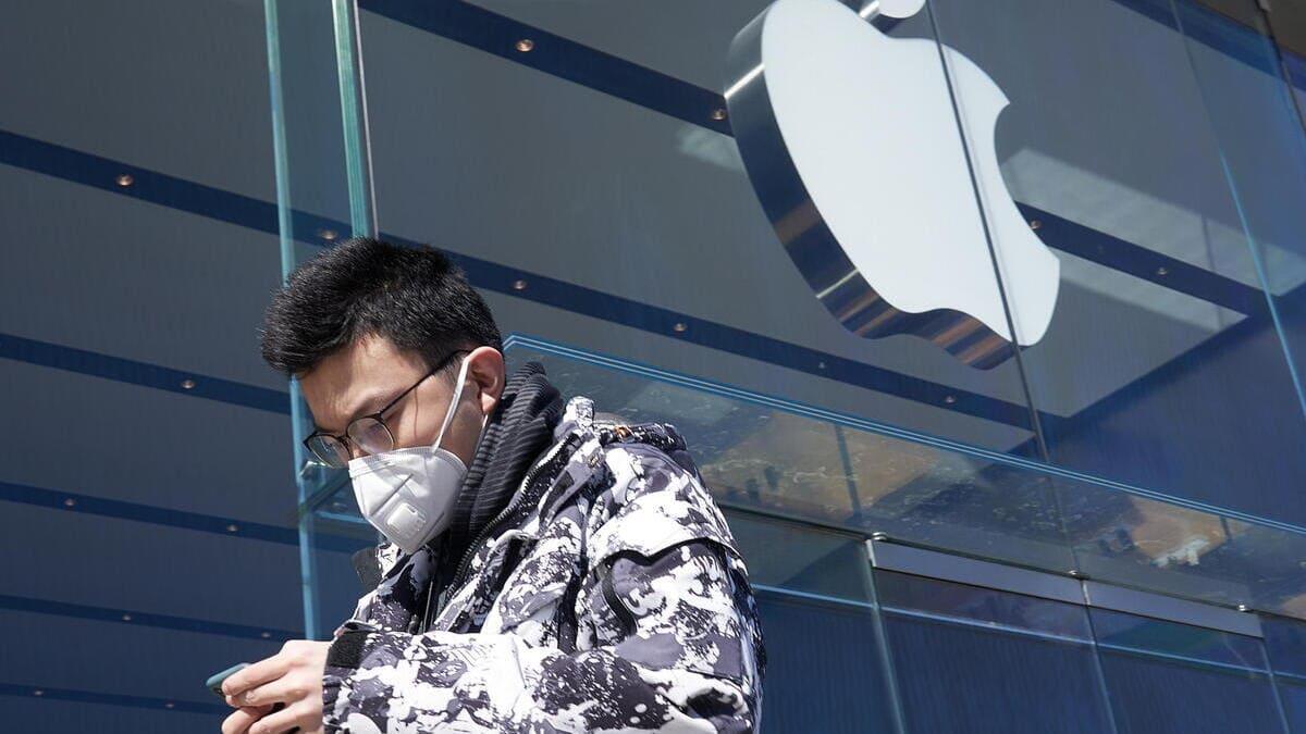Un ragazzo cinese guarda l'iPhone mentre passa davanti a un negozio della Apple in Cina