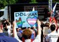 Manifestazione a Milano, un uomo alza un cartello pro ddl Zan