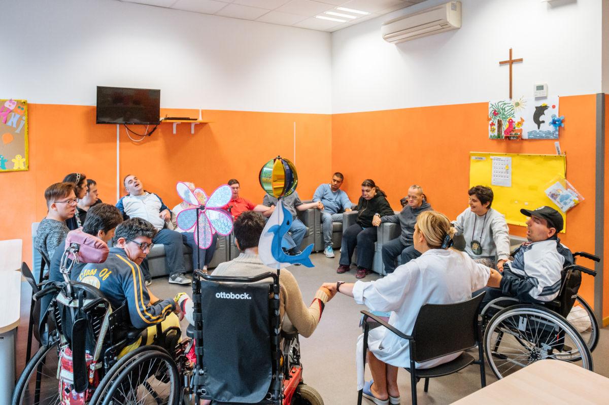 Attività di gruppo con i disabili in un locale della Fondazione Sacra Famiglia
