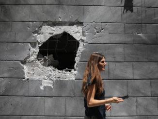 Donna davanti a un muro colpito da un missile ad Askelon, Israele