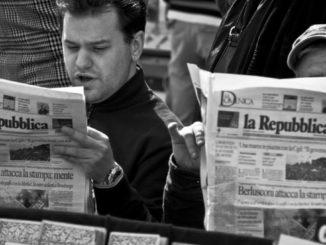 Due uomini sfogliano il quotidiano La Repubblica