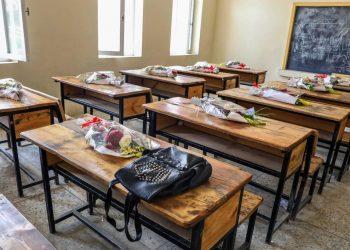 Scuola, cartelle e zaini appoggiati sui banchi in una classe