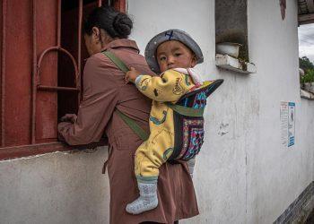 Una donna con il suo bambino in una provincia povera del Sichuan, in Cina