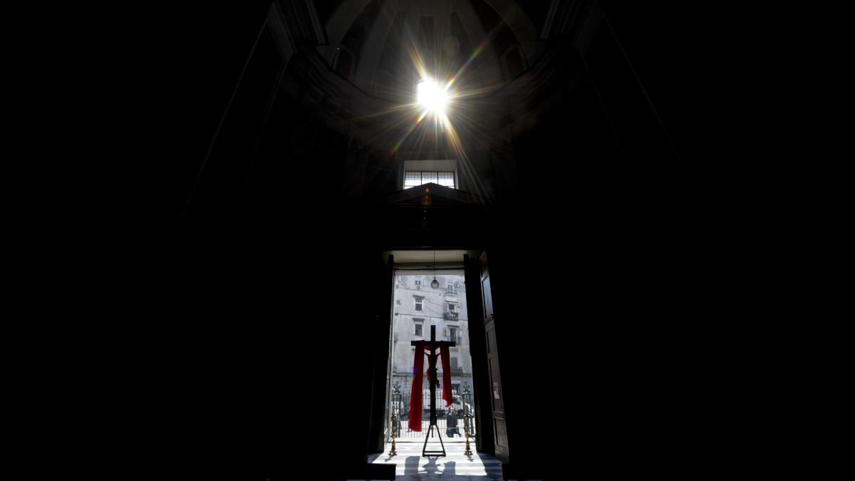 Fedeli in preghiera davanti al crocifisso all'esterno di una chiesa