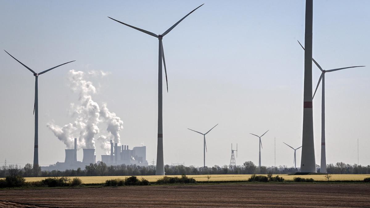 Centrale a carbone sullo sfondo della distesa di pale di un parco eolico