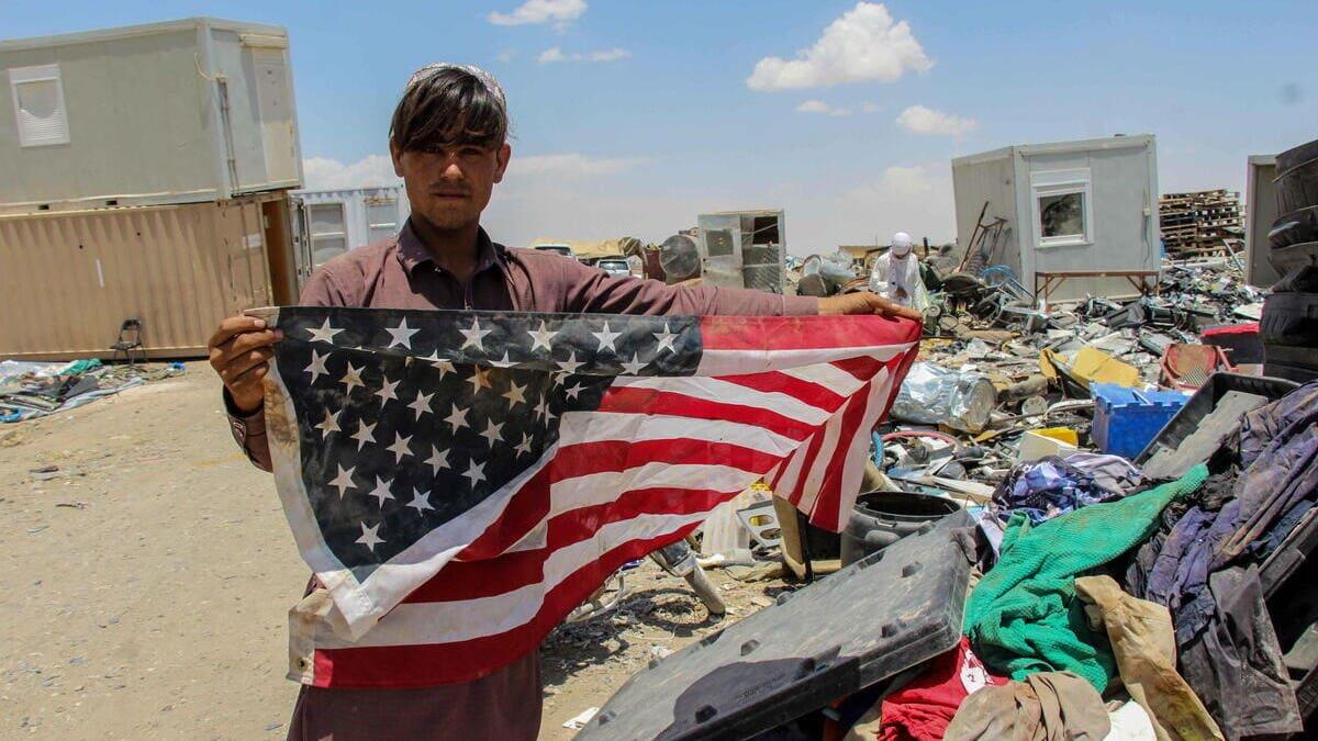 Un giovane in Afghanistan mostra la bandiera degli Usa