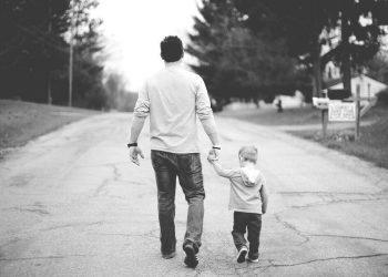 Un padre cammina insieme al figlio tenendolo per mano