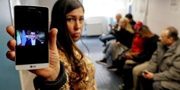 Una donna in fila per fare domanda per il reddito di cittadinanza mostra un telefonino con la foto del ministro Luigi Di Maio