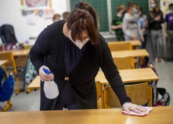 Un'inserviente a scuola igienizza i banchi per impedire la diffusione del Covid-19