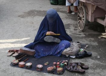 Una donna col burqa si guadagna da vivere in Afghanistan