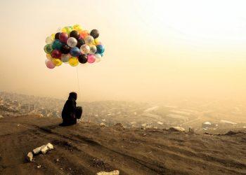 Venditrice di palloncini davanti a Kabul avvolta nella nebbia