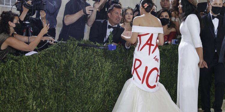 """Alexandria Ocasio-Cortez impacchettata nel suo tubino """"Tax the Rich"""" sul red carpet del Met in compagnia della stilista Aurora James (foto Ansa)"""