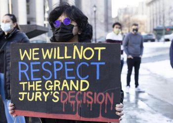 Una donna con un cartello di protesta durante una manifestazione BLM