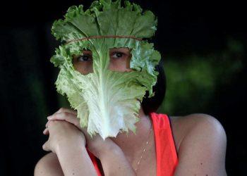 Un'attivista vegana indossa una mascherina di lattuga per sensibilizzare sull'origine animale di virus come il Covid (foto Ansa)
