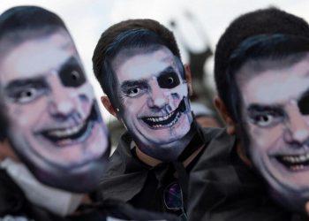 Manifestanti in piazza indossano maschere di Jair Bolsonaro rappresentato come un teschio per protestare contro il presidente del Brasile (foto Ansa)